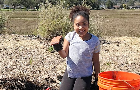 Young girl planting native flowers at Creekside