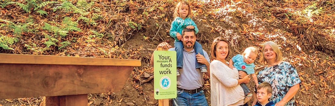 Family standing next to Measure A sign in Loma Alta Preserve