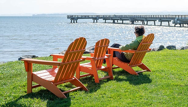 Woman sitting in orange Adirondack chair next to McNears pier