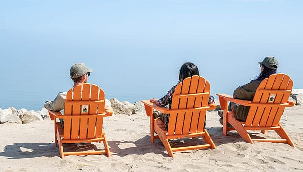 Three friends sitting on the beach in Adirondack chairs
