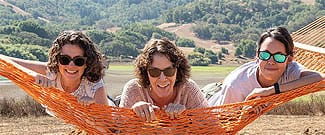 Three women smiling in an orange hammock