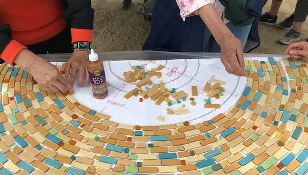 Volunteers' hands laying the mosaic tiles