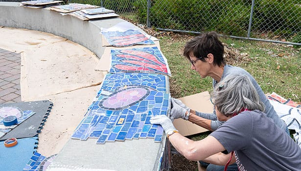 Artist and assistant constructing the mosaic