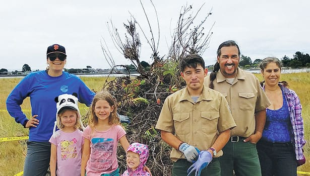 Parks staff and volunteers standing in front of a pile of pulled weeds